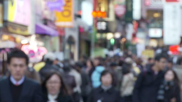 blurred shot of people walking along street - ソウル点の映像素材/bロール