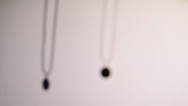 vídeos de stock, filmes e b-roll de blurred silhouette of human hand trying to catch a pendant, finally achieves to catch one pendant. dream time. - sombra