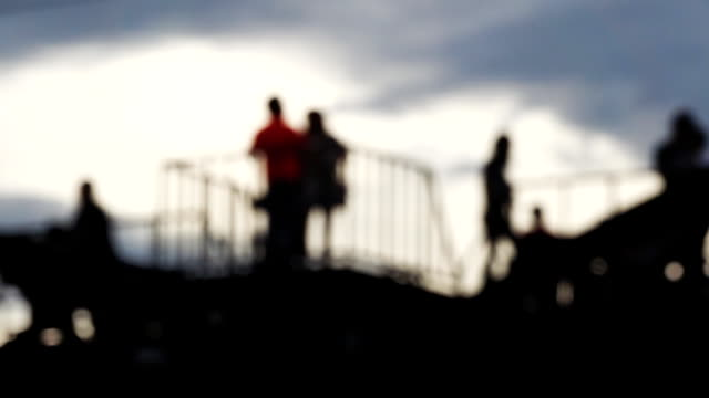 Blurred slow motion HD:  Tourists walking on the bridge over the River Kwai in Thailand.