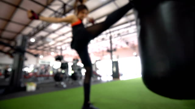 blurred - strong athletic female kicking a punching bag at the gym - self defense stock videos and b-roll footage