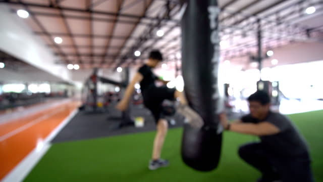 blurred - strong athletic man kicking a punching bag at the gym - bag stock videos and b-roll footage