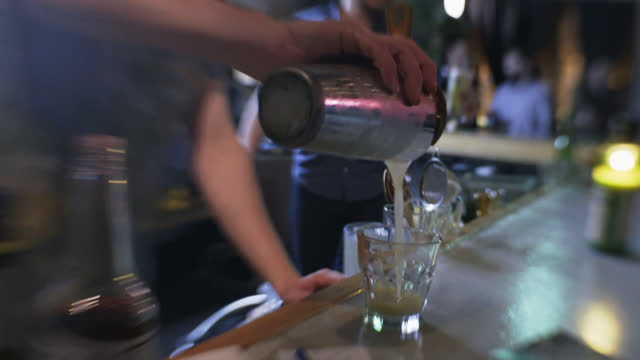 vídeos de stock, filmes e b-roll de blurry pov as bartender pours craft cocktail into glass from cocktail shaker - discoteca