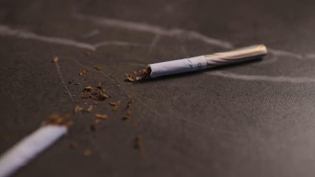 vídeos y material grabado en eventos de stock de blurry low angle of broken cigarette with tobacco lying on table - modo de vida no saludable