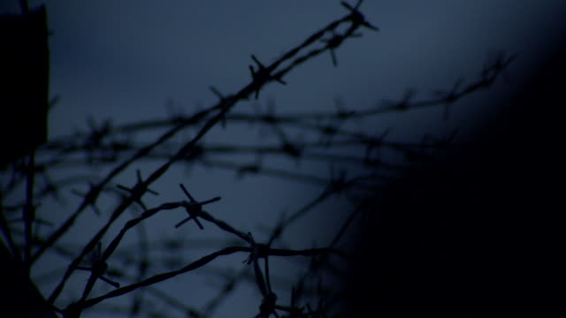 a blurry, silhouetted figure moves in front of trench paraphenalia, france. - barbed wire stock videos & royalty-free footage