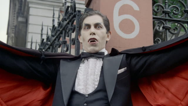 stockvideo's en b-roll-footage met movie camp style boy vampire scares and chases away men sitting around a fire, adult male vampire scaring people. - graaf dracula