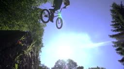 SLOW MOTION: Bmx biker jumps over the sun