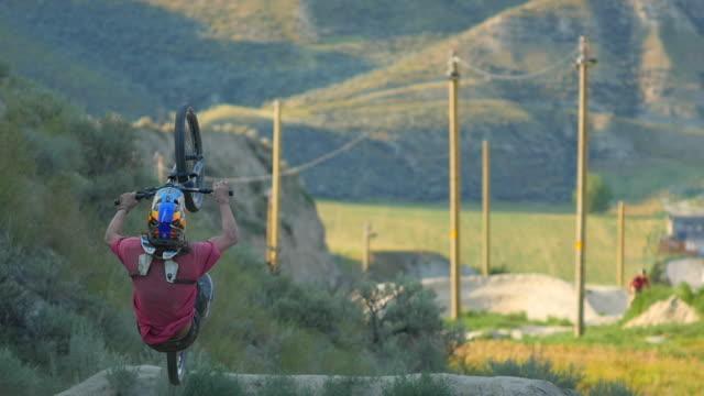 a bmx mountain biker does a back flip jumping trick on a dirt trail. - slow motion - マウンテンバイク点の映像素材/bロール