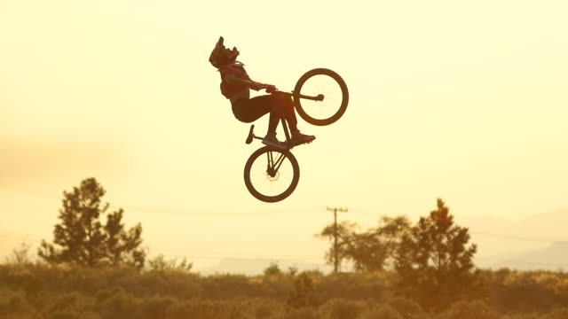 A bmx mountain biker does a double back flip trick and then crashes at sunset. - Slow Motion