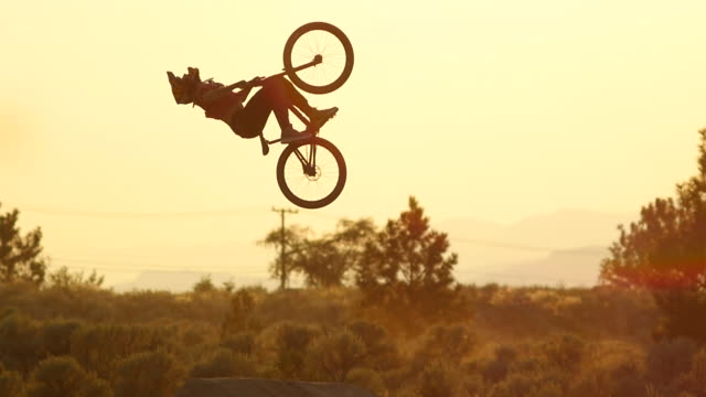 A bmx mountain biker does a double back flip trick and then crashes at sunset.