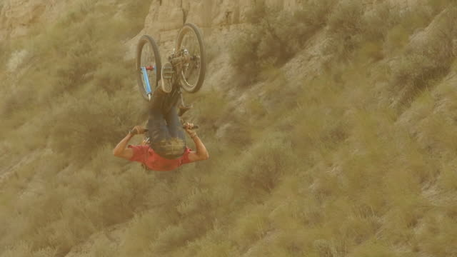 a bmx mountain biker does a front flip jumping trick with no hands. - slow motion - bmx cycling stock videos and b-roll footage