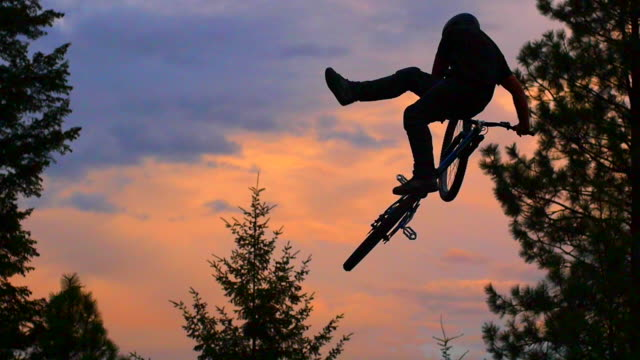 A bmx mountain biker does a jumping can-can trick at sunset. - Slow Motion