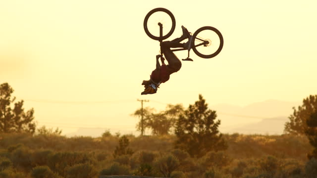 A bmx mountain biker does a jumping double back flip trick at sunset. - Slow Motion