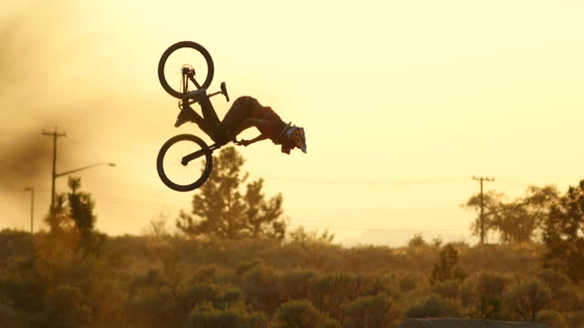 A bmx mountain biker does a jumping double back flip trick at sunset.