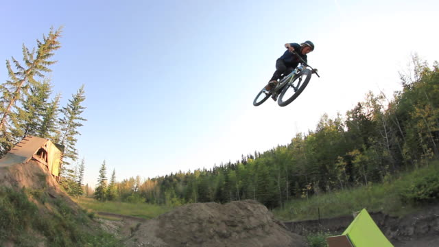 a bmx mountain biker does a jumping trick off a ramp. - slow motion - sports ramp stock videos and b-roll footage