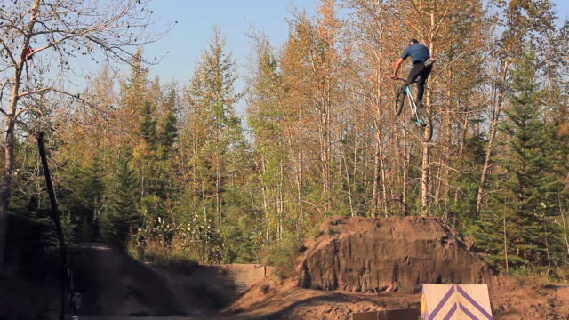 a bmx mountain biker does a jumping trick off a ramp. - sports ramp stock videos and b-roll footage