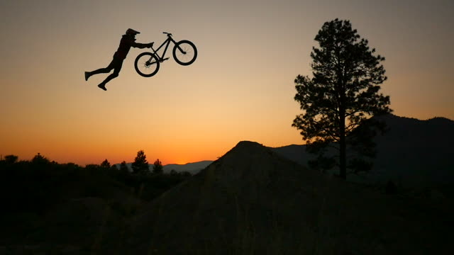A bmx mountain biker does a superman jumping trick at sunset. - Slow Motion