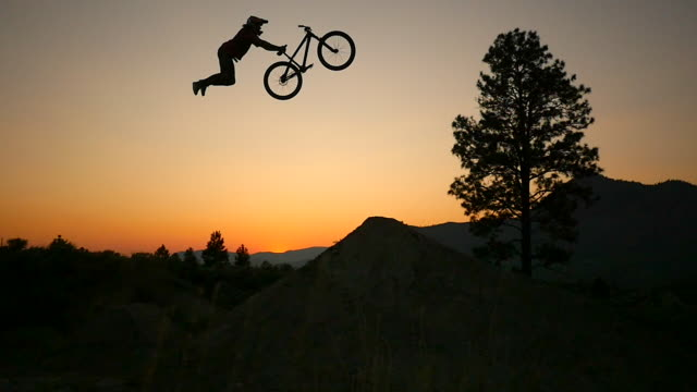A bmx mountain biker does a superman jumping trick at sunset.