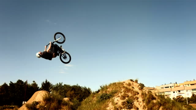 hd slow motion: bmx rider doing backflipping dirt jump - bmx cycling stock videos and b-roll footage