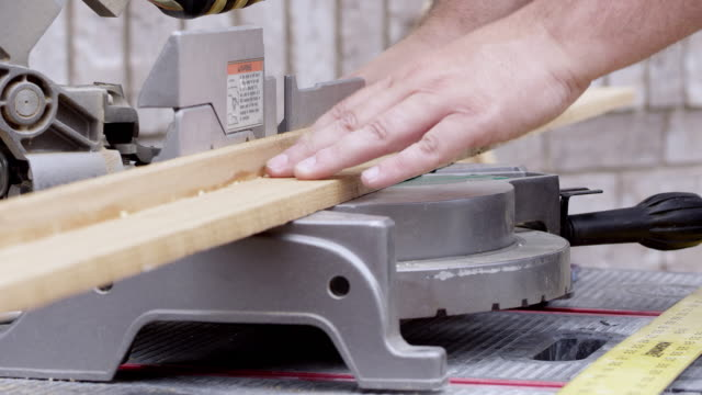 board being placed on miter saw and bening cut at an angle - おがくず点の映像素材/bロール