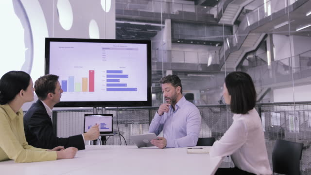 board meeting looking at sales performance presentation - カンファレンス点の映像素材/bロール