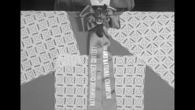 Board of crocheted napkins and table runner with ribboned rosette 'Grand National Champion Nationwide Crochet Contest 1952' and pan up to Miss...
