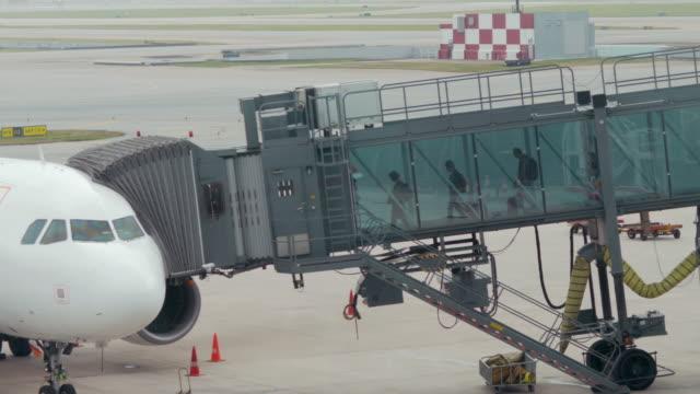 boarding-zeit am durchgang zu flugzeug auf dem flughafen nach flugzeug abheben - fluggastbrücke stock-videos und b-roll-filmmaterial