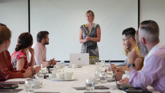 vidéos et rushes de sourires de salle de réunion - montrer la voie