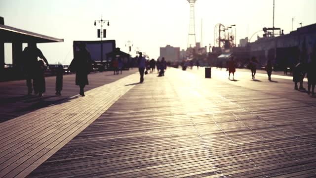 vidéos et rushes de promenade au coucher du soleil de coney island - sans mise au point and équilibre