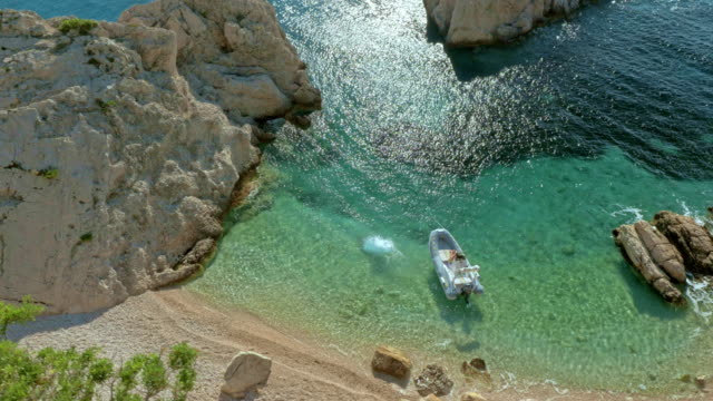 aerial boat anchored in bay by a wild beach - anchored stock videos & royalty-free footage