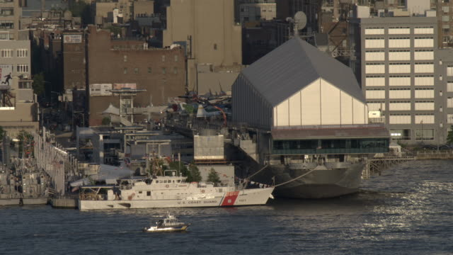 a nypd boat and a coast guard ship sits outside the interpid air and space museum in manhattan. - us navy stock videos & royalty-free footage