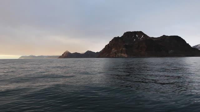 boat approaches cliffs - 崖点の映像素材/bロール