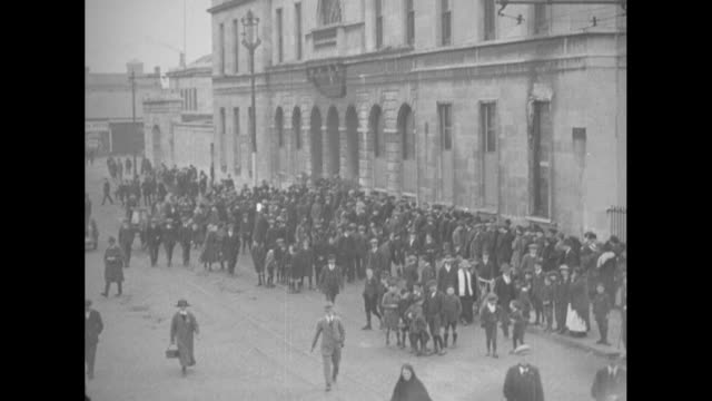 boat arrives bearing terence macswiney's flower-bedecked coffin with attendants wearing tam o' shanters; cork's city hall with a large crowd gathered... - 1920 stock videos & royalty-free footage