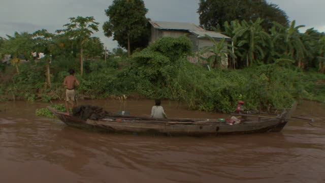 ms pov boat being passed by on banks of mekong river / phnom penh, cambodia - mekong delta stock videos & royalty-free footage