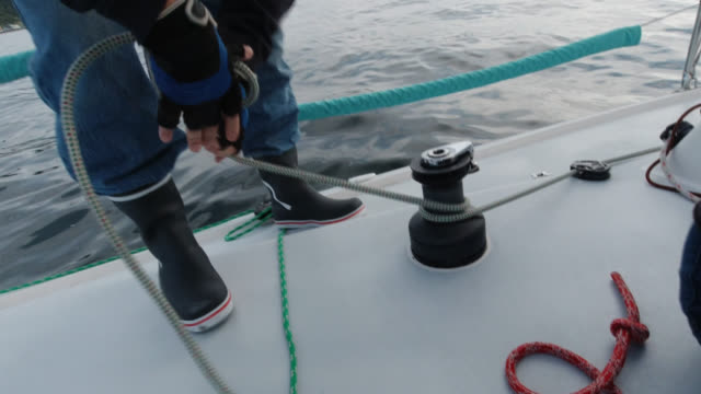 a boat captain in his sixties pulls a rope tight in a winch on his sailboat on the puget sound in washington while his crew sits on the deck and laughs contentedly - sailing team stock videos & royalty-free footage