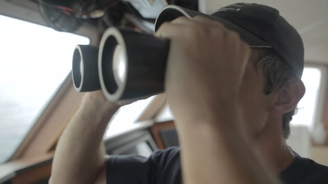 cu boat captain looking toward through binoculars / socorro islands, mexico - canocchiale video stock e b–roll