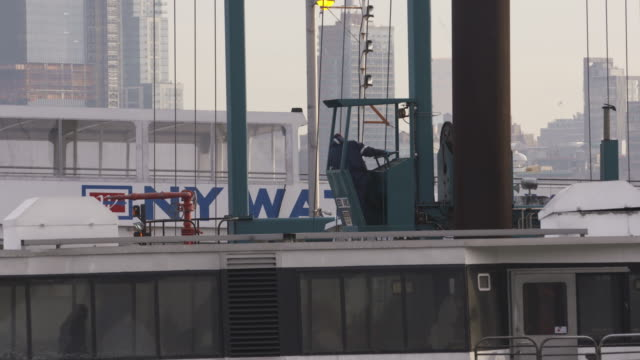 boat captain waits for pedestrians to enter ferry as he mans the wheel at top of ship. - 水上タクシー点の映像素材/bロール