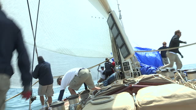 A boat crew manages ropes and sails on the J Class yacht Velsheda during a race.