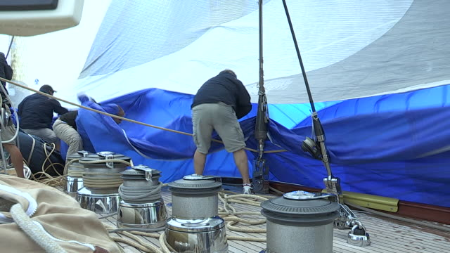 A boat crew works together to control the spinnaker on the the J Class yacht Velsheda during a race.