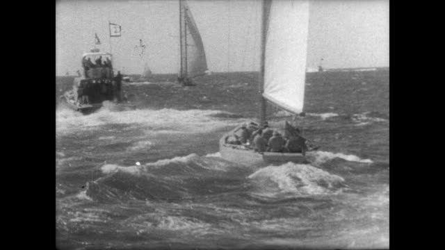 vidéos et rushes de boat crews and crowd on pier in newport / aerial showing spectator fleet of boats on water / intrepid and dame pattie race / choppy water challenges... - équipe de voile