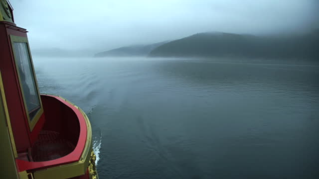 boat crosses Japanese lake on foggy day
