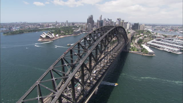 A boat crosses under Sydney Harbour Bridge near the Sydney Opera House.