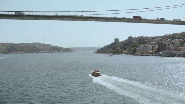 aerial boat crossing under the bosphorus bridge / istanbul, turkey - july 15 martyrs' bridge stock videos & royalty-free footage
