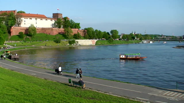 Boat crossing Visla river, Wawel castle is on the left. Poland, Krakow