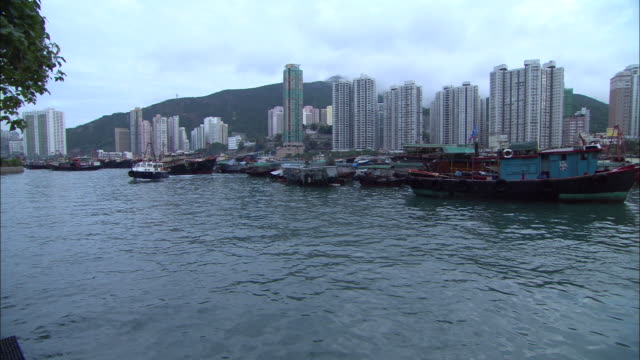 vidéos et rushes de a boat cruises along a harbor in hong kong, china. - aller tranquillement