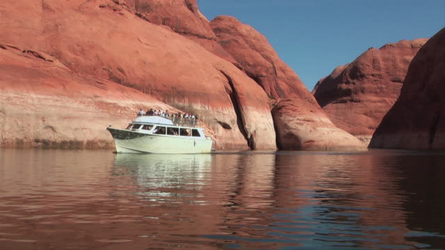 a boat cruises on lake powell. - lago powell video stock e b–roll