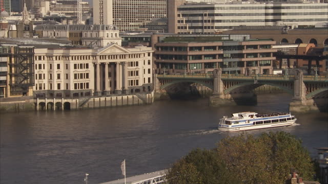A boat cruises on the River Thames. Available in HD.