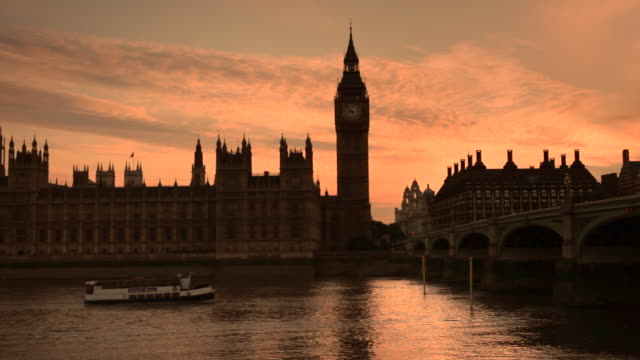 A boat cruises past the Houses of Parliament and Big Ben at sunset.