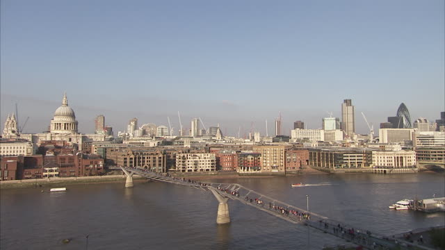 A boat cruises the River Thames as pedestrians cross the Millennium Bridge. Available in HD.