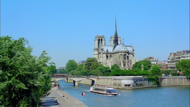 A boat cruises through the Seine River near the Notre Dame Cathedral in Paris, France.