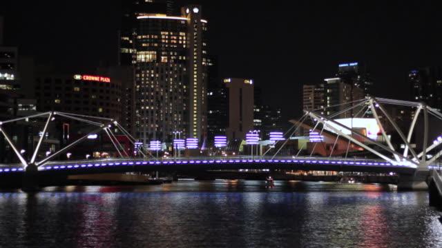 WS Boat cruises under bridge at night / Melbourne, Victoria, Australia